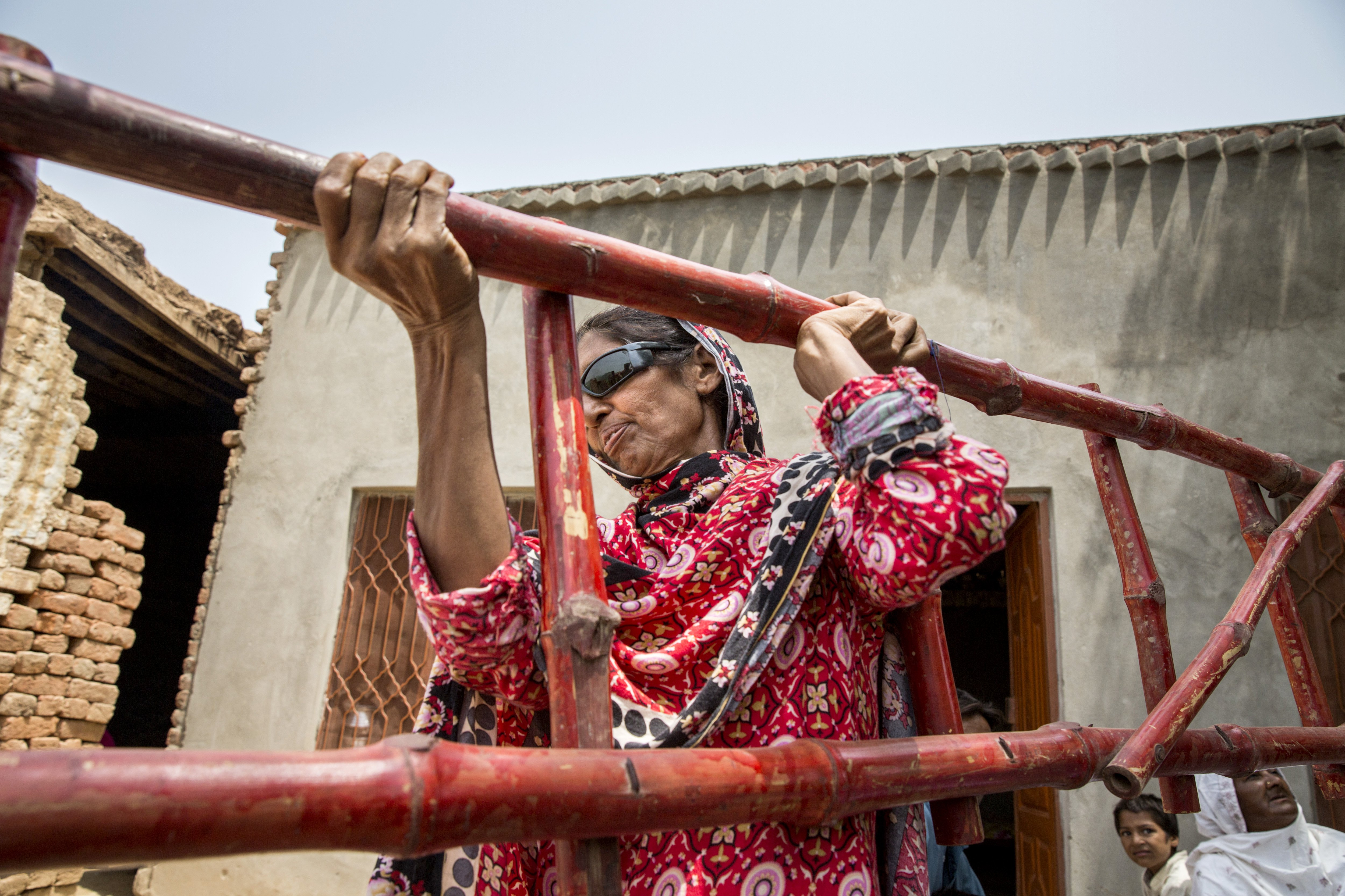 Kausar Shaheen lifts a ladder at her home in Manhiala, Chakwal District, Pakistan