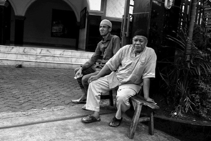 Two men sit outside a mosque in Kemang Timur, Jakarta © Arnaldo Pellini