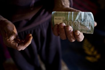 A Syrian refugee in Lebanon holds the money he will use to buy groceries