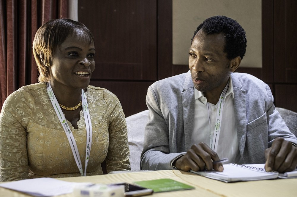 Africa Mini-Grids Community of Practice members Rhoda Mando and Abbas AbdulRafiu compare notes at the 2018 workshop in Abuja, Nigeria. Photo: Geraint Hill, 2018