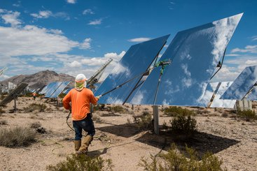 Workers clean heliostats at the Ivanpah Solar Project, California, USA