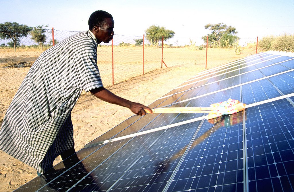 A man cleans a solar panel in Niger. Photo: Adam Rogers/United Nations Capital Development Fund, 2002 (CC BY-NC-ND 2.0)
