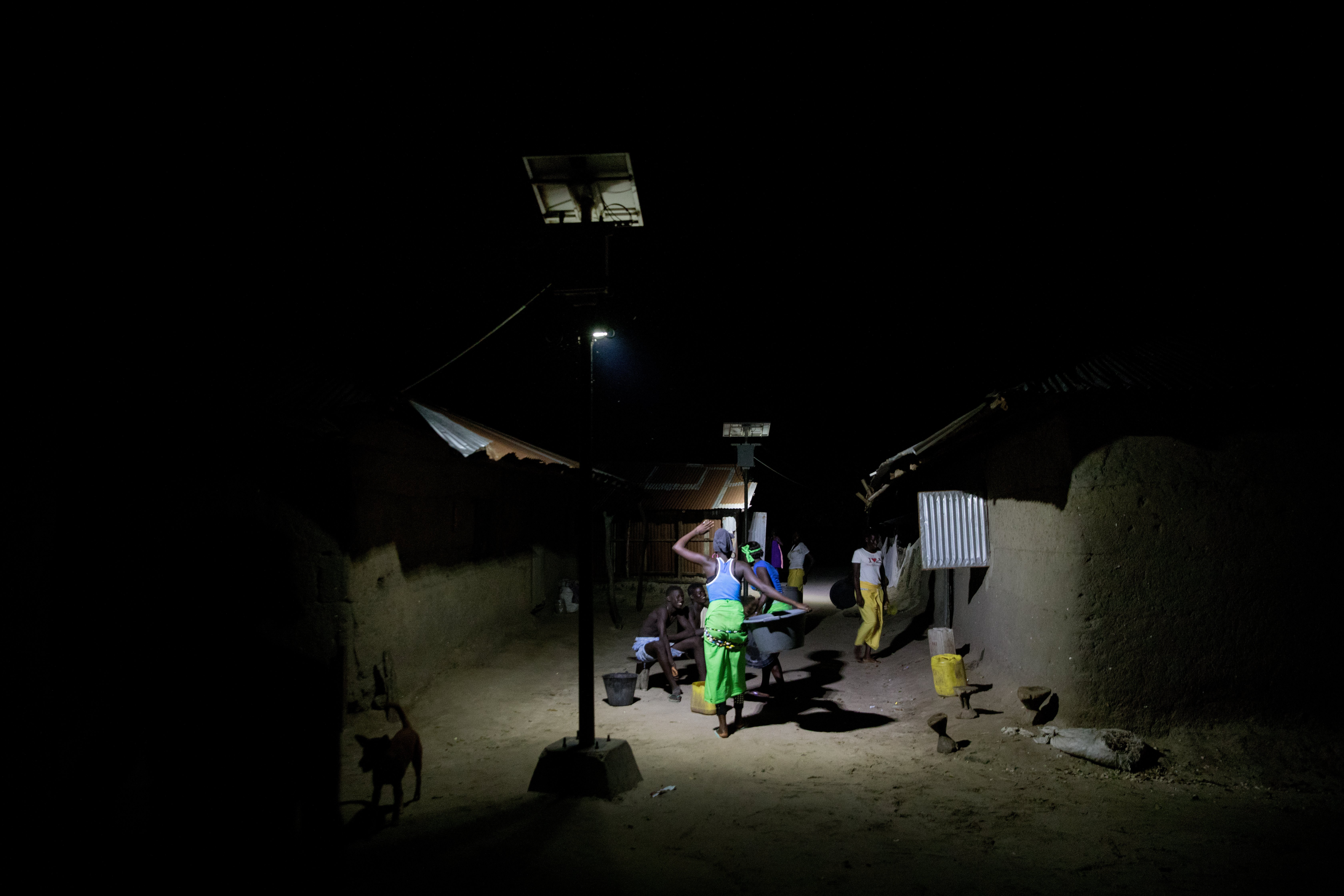 Villagers socialise under bright lights after dark following the installation of a solar power grid paid for by the community in Niomoune, Senegal.