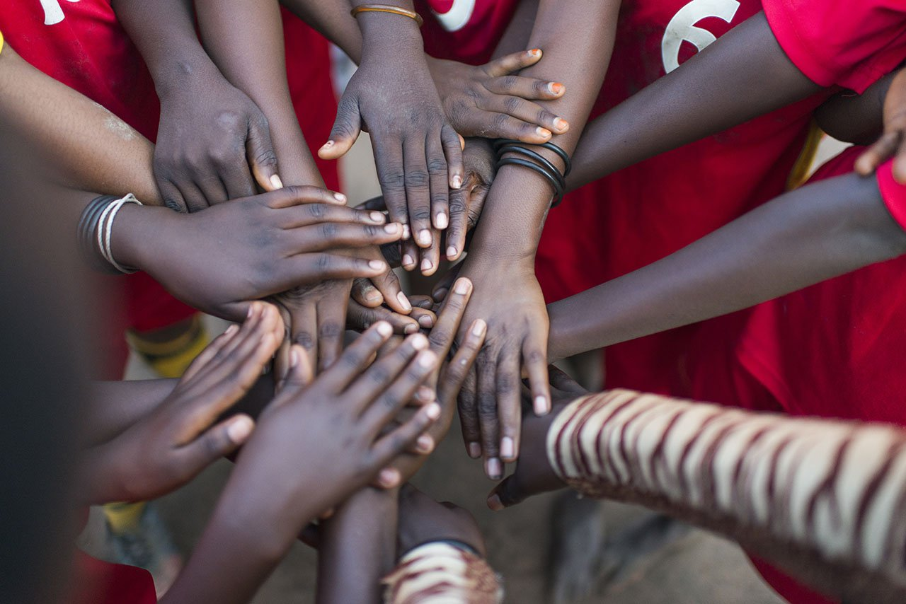 A refugee football team touches hands before a game at Lusenda refugee camp