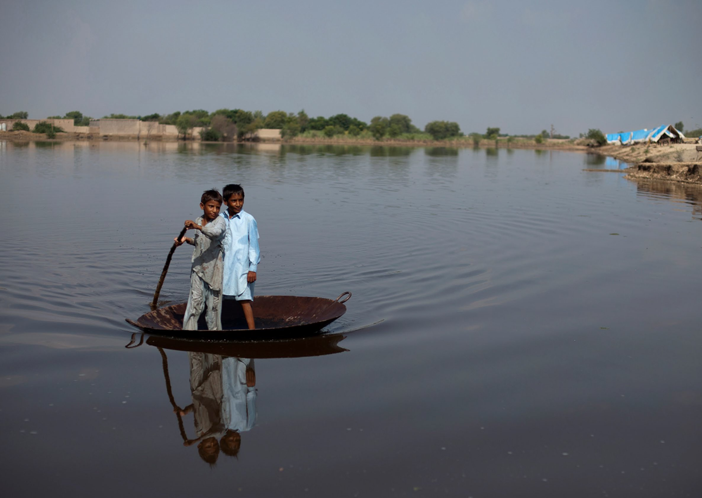 Boys use a large steel pot as a raft to cross an expanse of flood water in Pakistan in 2011