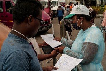 Health and Land Transport Agency (ATT) staff check passenger lists at Andohatapenaka Bus Station, Madagascar