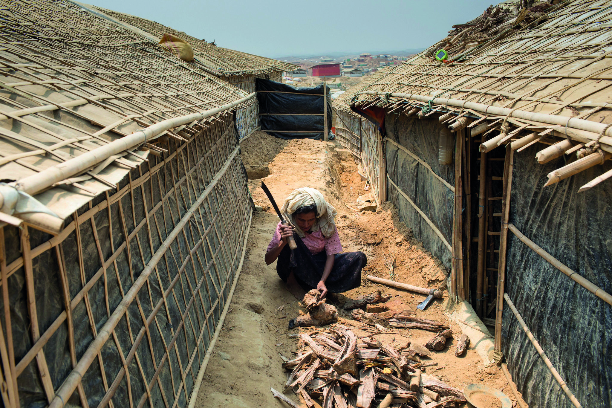 A Rohingya refugee chops firewood for cooking in Kutupalong megacamp