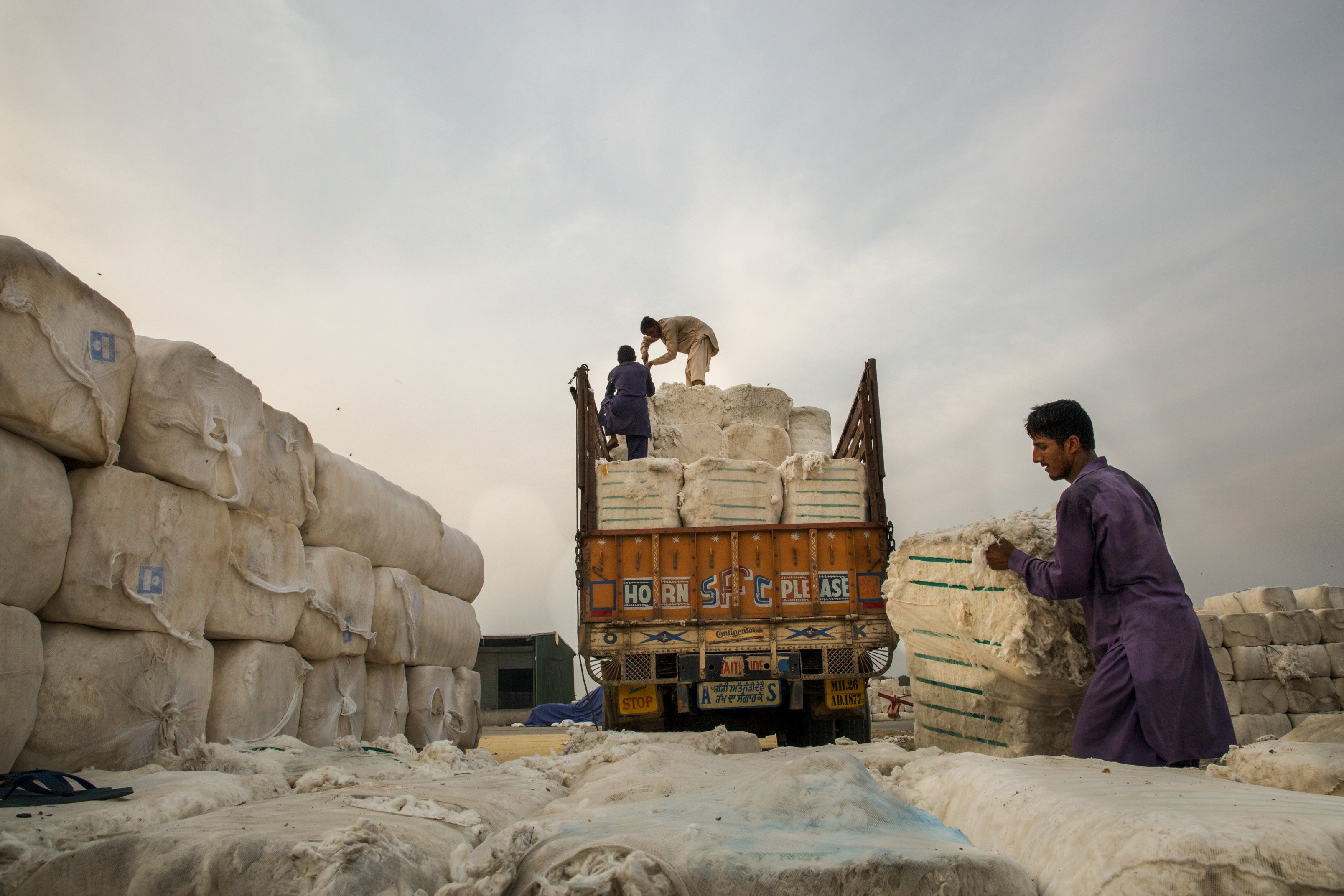 An Indian truck carrying cotton bales is being offloaded by the Pakistani workers at the Wagah-Attari Cargo Terminal