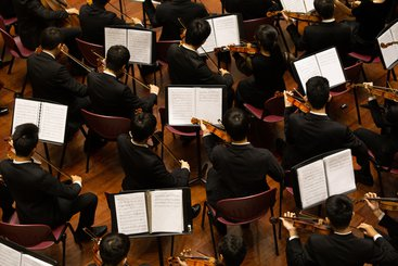 An image showing the strings section of an orchestra from above, with musicians seated and playing on violins.