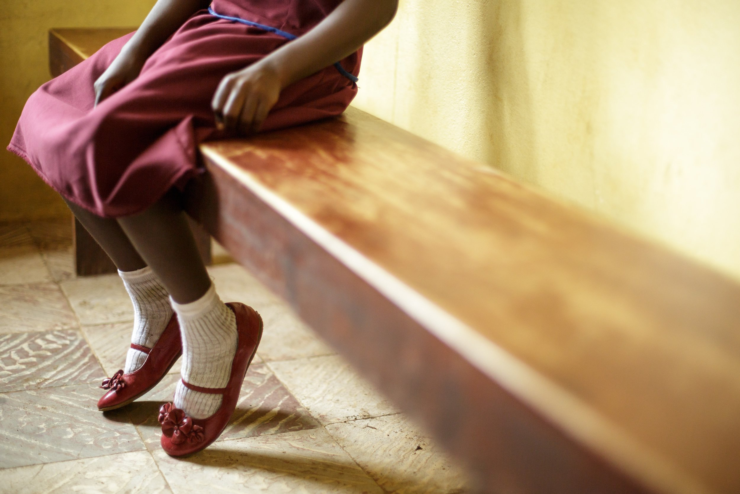 A young girl sits on a bench. Photo UNICEF/Olivier Asselin CC BY-SA 2.0