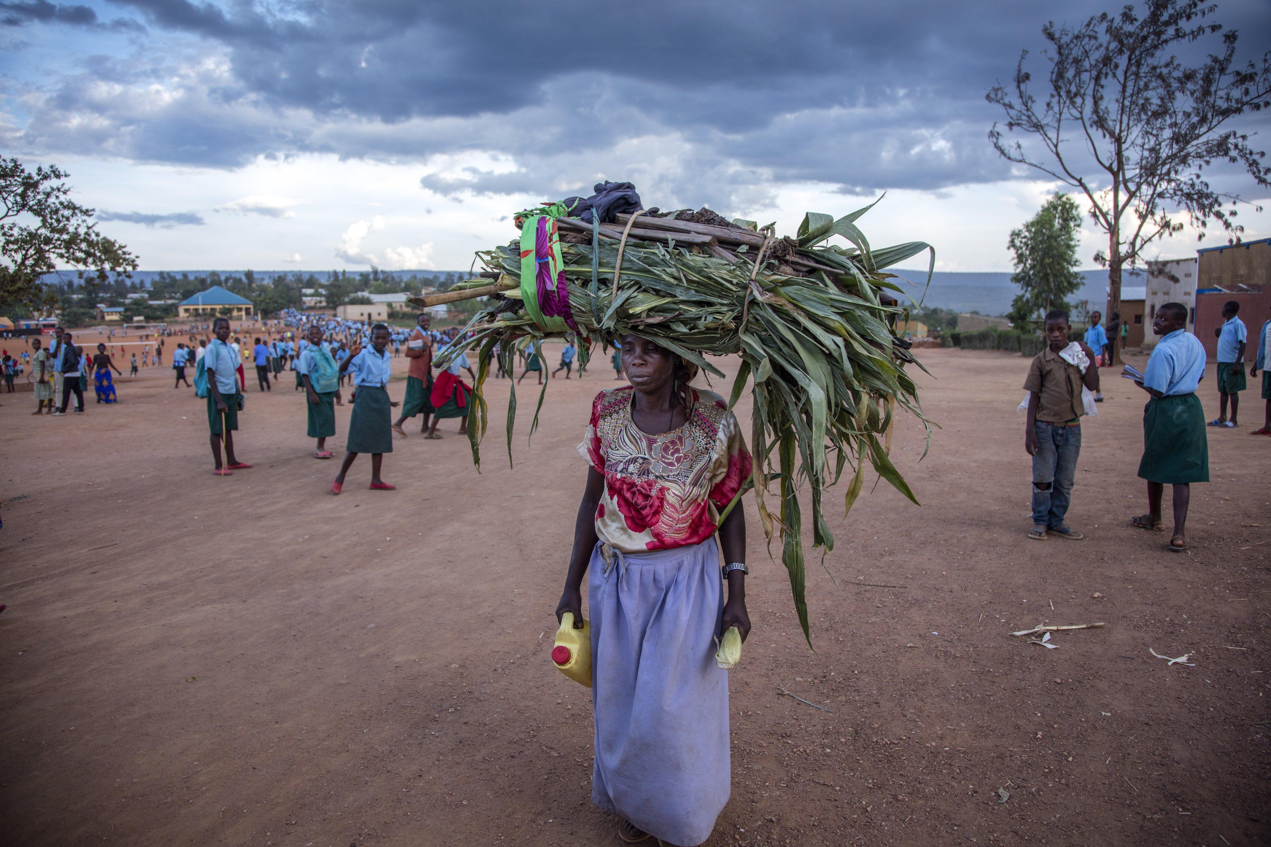 A woman carries grass for her cows through Mahama refugee camp in Kirehe, eastern Rwanda