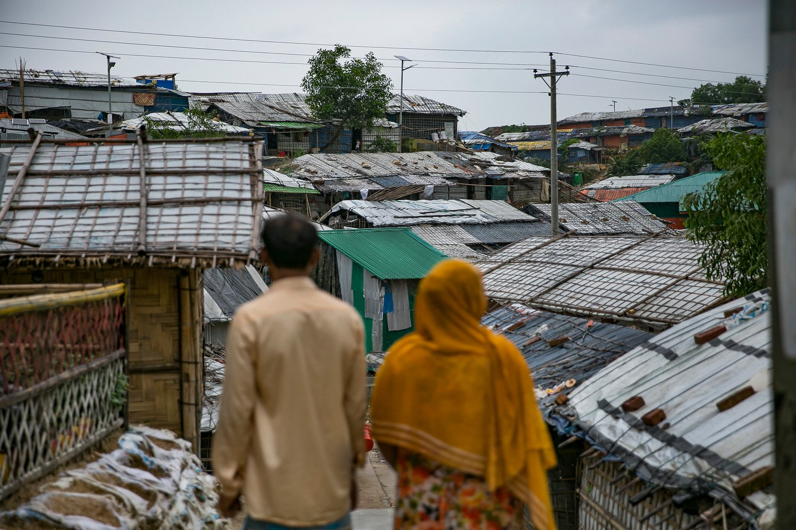 Rohingya couple pose for a photo in Balukhali camp outside their home