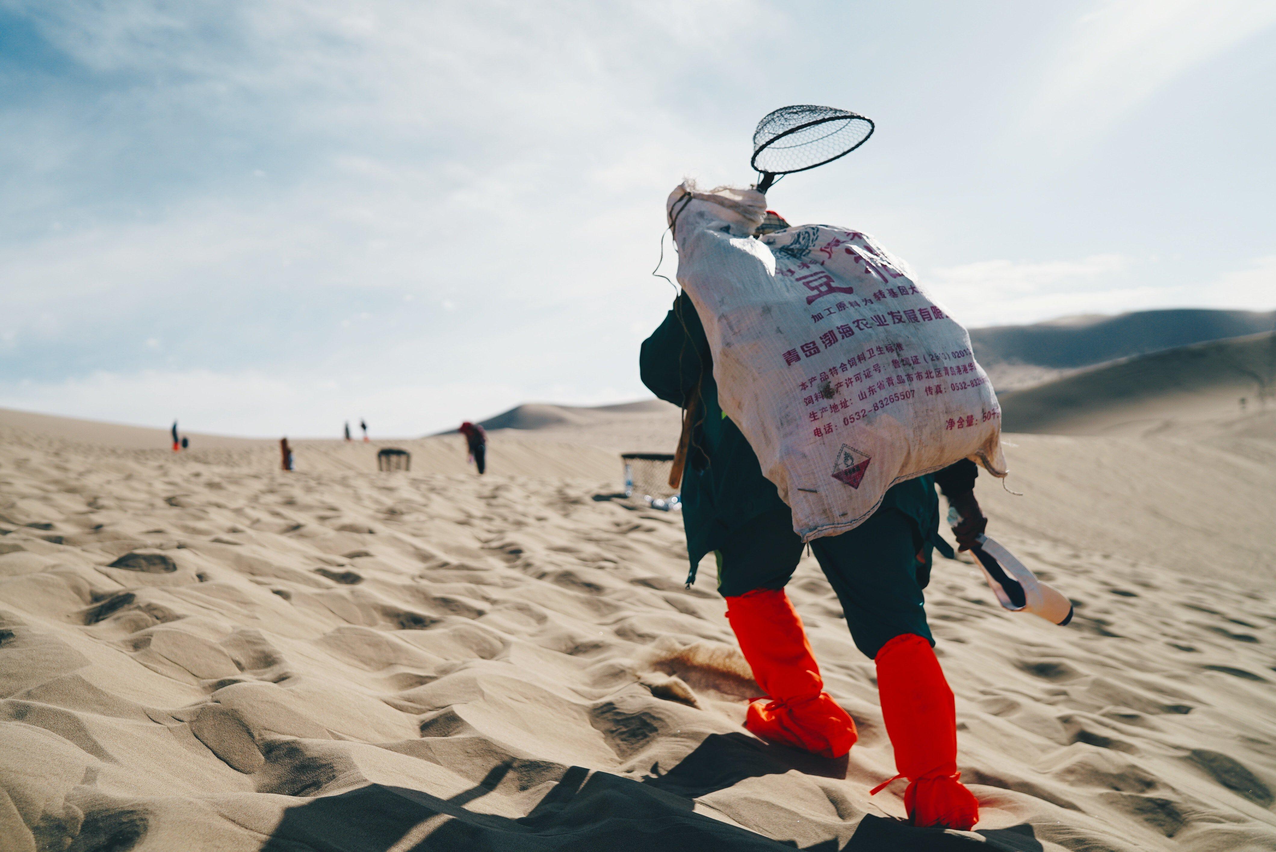 Man carries an empty net uphill in Dunhuang, Jiuquan, China. Photo: Steve Long/Unsplash